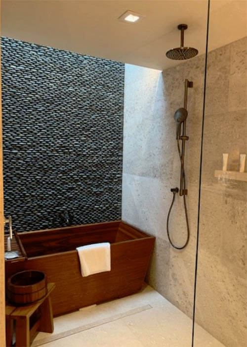 Wooden bathtub inside upscale shower stall