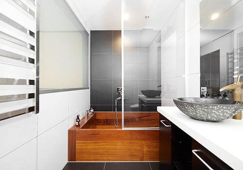A deluxe wooden bathtub in a hotel bathroom